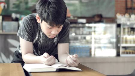 nerd : cute Asian boy reads books while waiting for his mother to buy drinks in the cafe.