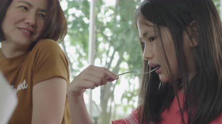 baby chicken : Asian Child Girl is eating breakfast by fork . Stock Footage