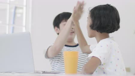 sitting floor : Young asian boy and girl playing with laptop computer at home. Children are playing online game on a laptop computer together. Dolly shot 60fps. Stock Footage