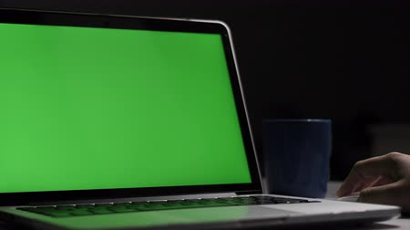 over the shoulder view : Over the shoulder shot of a young boy using on laptop computer on desk, looking at green screen. Dolly shot 60fps. Stock Footage