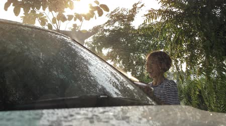 spugna : Happy Asian girl washing car on water splashing and sunlight at home : Slow motion shot