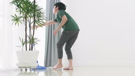 paçavra : Asian young boy help family cleaning the house using a mop.