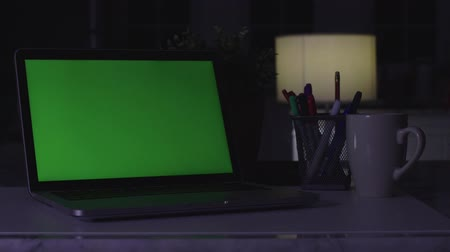 собственность : Laptop with green screen. Dark office.  Perfect to put your own image or video.Green screen of technology being used. Chroma Key laptop