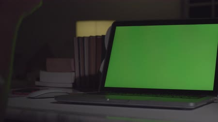 рабочий стол : Laptop with green screen. Dark office. Dolly shot. Perfect to put your own image or video.