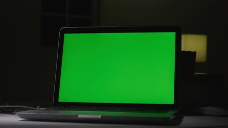 собственность : Laptop with green screen. Dark office. Dolly shot. Perfect to put your own image or video.