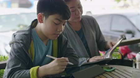 risonho : Asian boy is playing tablet computer and talking with his mother, smiley face.