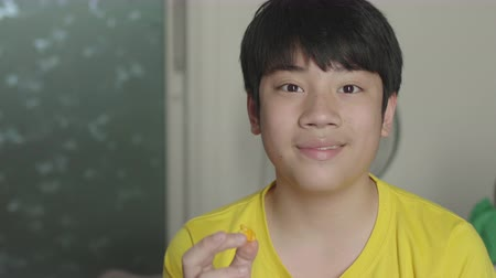 премьера : Asian boy watching movies and eating popcorn, enjoying at home.