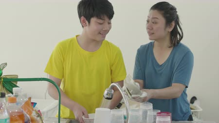 housekeeper : Happy family mother and son dishwashing together at home with smile face Stock Footage