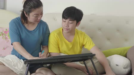 soutien scolaire : Mother with son doing homework in the bedroom. Mom teaches son how to understand fundamental analysis. Vidéos Libres De Droits