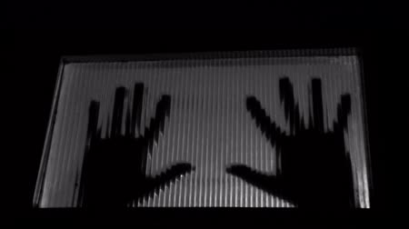 bater : Trapped man knocking on door, hands shadow abstract. Black and white.