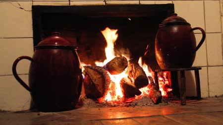 cozy : Chimney, kitchen hearth of burning rural house. Ancient scene cooking with two stews in trivet to the fire. Fireplace, stove on at home farmhouse. Scene two ancient cooking pots on trivets fire Stock Footage
