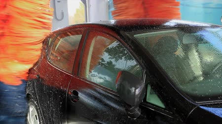 lathering : Processes in the complete sequence of washing a black car on a Tunnel automatic car wash - Spinning reels with soap and water in the process of washing the car bodywork Stock Footage