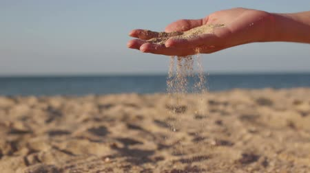 sifted : Close up view of sea sand running through a womans hands against a blurred ocean. conceptual of a summer vacation Stock Footage