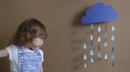 pesadelo : conceptual portrait. Little girl on gray background play with drop shapes and cloud