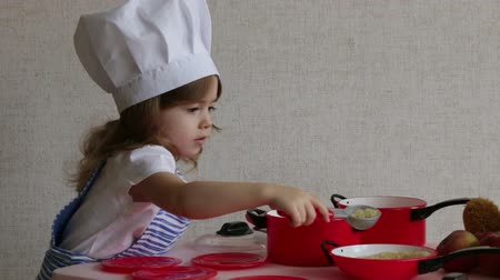 gives you : Portrait cute little girl dressed as a chef cook food Stock Footage
