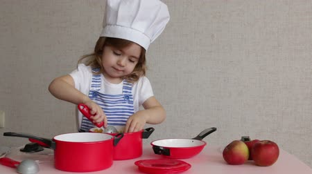 gives : Portrait Adorable little girl in chef hat cook food