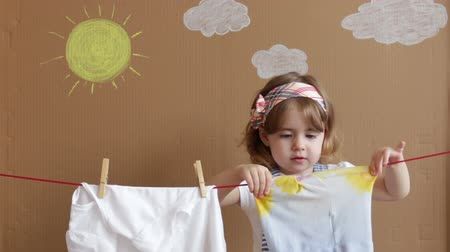 varal : The little pretty girl Hand Putting Clothespin and hangs out to dry a clothes. Conceptual housework. baby helps mom