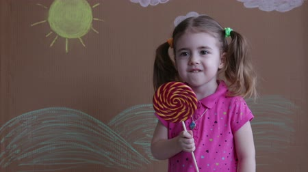 doces : portrait of emotional girl with big sugar lollipop, kid eat sweets. Beautiful little girl with lollipop Stock Footage