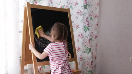 authenticity : child wipes a rag drawing with a black board Stock Footage