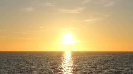 horizont : The bright sun is setting over water with gentle waves