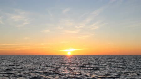 göl : The bright sun is setting over water with gentle waves