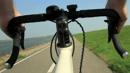 View on a steering wheel of a racing bike riding on a bicycle path in the country.