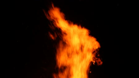 пламя : Wild yellow flames from a burning wood fire against a black background.