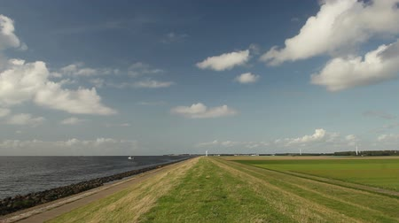 levee : Dike on a polder in the Netherlands. The IJsselmeer on the left (former Zuydersea) and the Noordoostpolder with farmland on the right. The former island of Urk lies on the horizon.