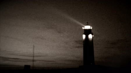 világítótorony : Vintage style footage of a lighthouse with turning light beam. Stock mozgókép