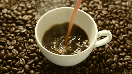 xícara de café : Pouring coffee in a white cup with roasted coffee beans in the background.
