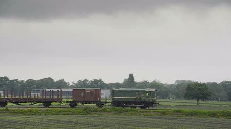 lokomotif : Old diesel freight train pulling various railroad cars in the countryside.