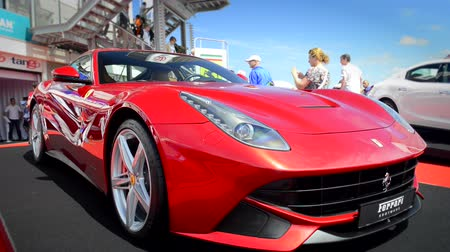berlinetta : Ferrari F12 Berlinetta supercar in the paddock at the Zandvoort race track during the 2014 Italia a Zandvoort day. People are watching the cars.