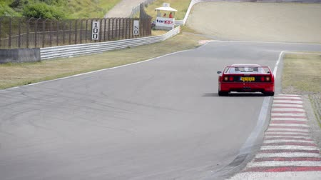 berlinetta : Ferrari F40 and 360 Modena sports car driving through a corner  during the Italia a Zandvoort event at the Zandvoort race track.  Stock Footage