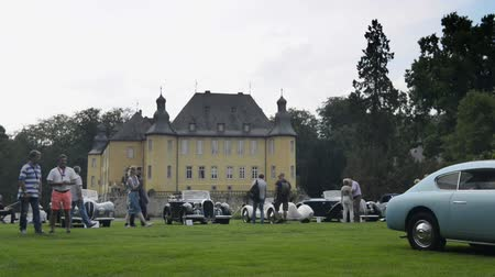 alfa : Various classic cars parked on the grass in front of Schloss Dyck during the 2014 Classic Days event. Time lapse clip with people moving around.
