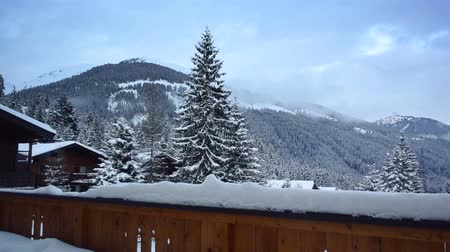 faház : Time lapse clip of clouds moving over a snowy mountain seen from the snow covered balcony of a chalet in the mountains.