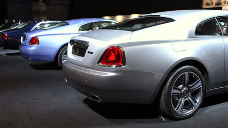 roll : Two Rolls Royce Wraith luxury coupe cars on display at the Amsterdam motor show. A woman walks past the cars. Stock Footage