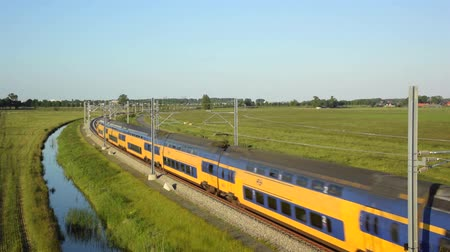 "mozdony : Intercity train of the Dutch Railways (NS- Nederlandse Spoorwegen)  passing on a railroad track in the country side at the end of the day."",""train, passenger train, Intercity, commuter train, commuter, passing, locomotive, transport, transportation, railr Stock mozgókép"