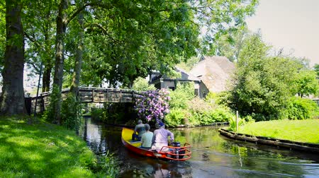 apostador : Tourists in boats on the canal of the famous village of Giethoorn in Overijssel, The Netherlands on a sunny summer day.