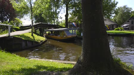 apostador : Tourists in a tour boat on the canal of the famous village of Giethoorn in Overijssel, The Netherlands on a sunny summer day.
