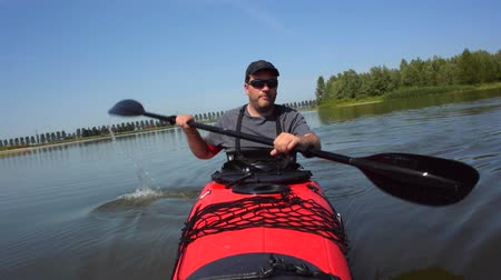kayak : Man paddling in a red kayak on a calm lake in nature during a beautiful summer day. Stock Footage