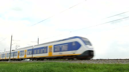 locomotiva : KAMPEN, THE NETHERLANDS - AUGUST 28, 2015: Commuter train passing on an elevated railroad track in the country side at the end of the day.