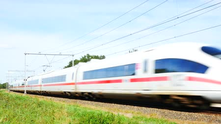 almanca : ZEVENAAR, THE NETHERLANDS - SEPTEMBER 10, 2015: ICE High Speed Train driving past in the country during a beautiful summer day. Stok Video