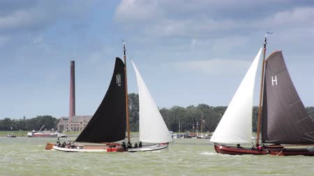парусное судно : Skutsje classic sailboats during the traditional annual Skutsje sailing race in Friesland, The Netherlands.
