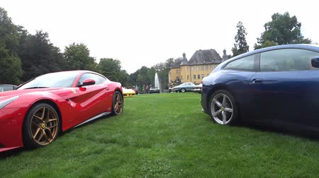 berlinetta : Ferrari F12 Berlinetta and Ferrari GTC4 Lusso Grand Tourer Italian sports car on display during the 2017 Classic Days event at Schloss Dyck. People in the background are looking at the cars. Stock Footage