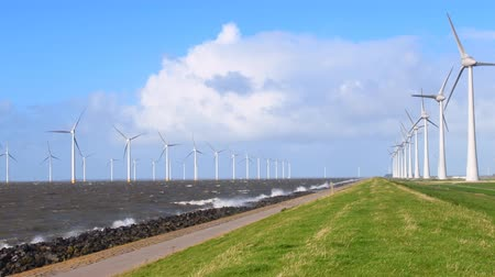 levee : Windturbines in an October fall storm at the IJsselmeer in The Netherlands.
