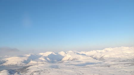 polar circle : Aerial view over the snowy mountains of Northern Norway in the Arctic Circle during a beautiful winter day. Stock Footage