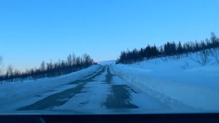 маркировка : Driving on an icy road on the island Senja in Northern Norway during a beautiful winter sunset.