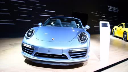 sala de exposição : Porsche 911 Turbo and 911 Turbo S Cabriolet sports cars on display at the 2018 European motor show in Brussels.  Stock Footage
