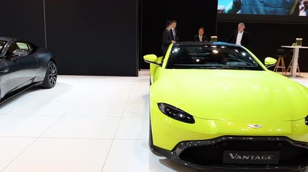 gt : Aston Martin Vantage in bright green and DB11 Coupe exclusive Grand Tourer sports cars on display at the 2018 European motor show in Brussels. Stock Footage