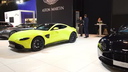 tourer : Aston Martin DB11 Convertible and Vantage in bright green exclusive Grand Tourer sports cars on display at the 2018 European motor show in Brussels.